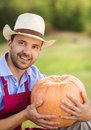 Gardener with huge pumpkin young holding pumpking in the garden Stock Photo