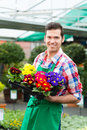 Gardener in market garden or nursery florist flower shop greenhouse Royalty Free Stock Photo