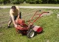 Gardener trying to start a older garden tiller gearden Stock Photography