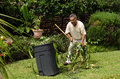 Gardener at work raking plant cuttings in yard Stock Photo