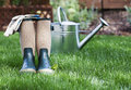 Gardening boots on lawn rubber and woven cloth green with metal watering can blurred in background a concept for spring Royalty Free Stock Photo