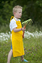 Gardening cute little boy with rake outdoors an yellow apron Royalty Free Stock Photography