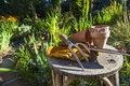Gardening tools utensils gloves and flower pots resting on a stool in a green garden Royalty Free Stock Photography