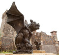 Gargoyle with castle a sits along side of his twin in front of the that they guard Stock Image