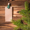 Garland with cute empty little kraft paper stickers hanging on a rope on wooden clothespins. Rustic Christmas decoration.