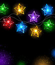 Garland of stars electric colored lamps in the shape on a black background Royalty Free Stock Photo