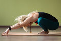 Garland yoga pose portrait of sporty beautiful blond woman in sportswear working out indoors doing squat variation of malasana on Royalty Free Stock Photos