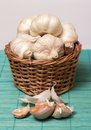 Garlic on basket some heads and a container plain background Royalty Free Stock Image
