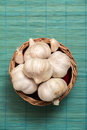 Garlic on basket some heads and a container plain background Royalty Free Stock Images
