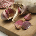 Garlic bulbs and cloves on wooden chopping board Stock Photography