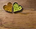 Garlic and calcium supplements pills in metal hearts over aged wooden board Royalty Free Stock Photography