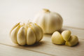 Garlic cloves and bulb on chopping board with copy space Stock Photo