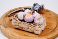 Garlic and garlic press bulbs in a wicker basket with a on a wooden board Royalty Free Stock Photo