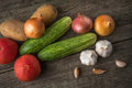 Garlic, onion, cucumber, potatoes and tomato on an old table Royalty Free Stock Photo
