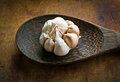 Garlic with peel on ladle wood in the kitchen Stock Image