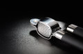 Garlic press on a black grained surface Stock Photography