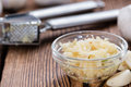 Garlic press with fresh garlic on rustic wooden background Royalty Free Stock Photo