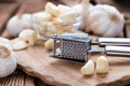 Garlic press with fresh garlic on rustic wooden background Royalty Free Stock Photos