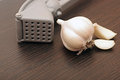 Garlic press and garlic on wood board Royalty Free Stock Image