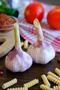 stock image of  Garlic, red tomatoes, dry Georgian spices for gourmets, olive oil, pasta on a wooden table. The concept of cooking, natural