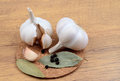 Garlic on a table with a bay leaf and black pepper in a polka dot Royalty Free Stock Photos