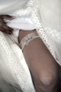 Garter on the leg of a bride slim sexy in wedding luxury dress Stock Photos