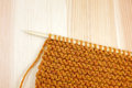 Garter stitch in orange yarn on a knitting needle deep pine board Royalty Free Stock Photo