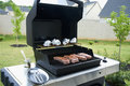 Gas grill with open lid and rib eye steaks Royalty Free Stock Images