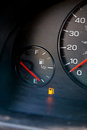 Gas guage empty a in a car reads and shows the warning light to let the driver know they are out of and need to refuel Stock Photo