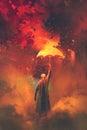 Gas mask man holding burning umbrella on fire background