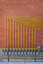 Gas meters on brick wall row of natural with yellow pipes building Stock Photography