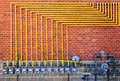 Gas meters on brick wall row of natural with yellow pipes building Royalty Free Stock Images