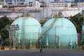 Gas storage tank in oil refinery industry site with urban scen b Royalty Free Stock Photo