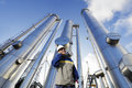 Gas worker and pipelines oil installation with an oil talking in phone towers Stock Photography