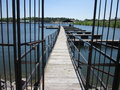 Gate and boat fishing docks a beautiful wrought iron leading to a wooden dock on a lake for boats Royalty Free Stock Images