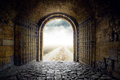 Gate opening to endless road leading nowhere old arch country hopelessness and great unknown concept Stock Photo