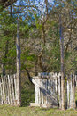 A gate partially open leading into the woods