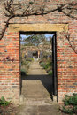 Gateway in brick wall in cottage garden. Royalty Free Stock Photo