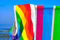 Gay beach a swimsuit patterned with the rainbow flag on a deck chair of different colors on the Stock Image