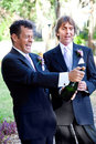 Gay couple opening champagne handsome at their wedding a bottle of Royalty Free Stock Photo