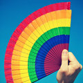 Gay hand fan someone holding a painted with the colors of the pride flag over the blue sky with a retro effect Royalty Free Stock Photography