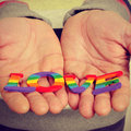 Gay love with a retro effect young man holding in his hands letters painted as the pride flag forming the word Stock Photos