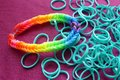 Gay pride loom band bracelet rainbow colored and unwoven turquoise bands on a purple background Stock Photography