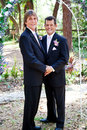 Gay wedding couple in love handsome male standing under a beautiful floral archway Royalty Free Stock Images