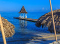 Gazebo on beach pier montego bay jamaica thatch hut umbrellas sandy with in background Stock Photo