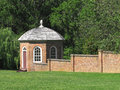 Gazebo and brick wall enclosed attached to a with green lawn in front trees in the background Royalty Free Stock Photos