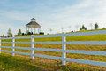 Gazebo in the new city park behind white fence Royalty Free Stock Images