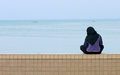 Gazing from the sea wall muslim girl in traditinal hijab sitting on looking out at distant fishing boats in georgetown malaysia Stock Photo