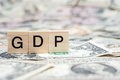 GDP or Gross domestic product wooden block on US Dollar bank note Royalty Free Stock Photo