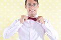 Geek adjusting bow tie nerd styled man Stock Image